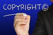 picture of plagiarism  - Business concept image of a businessman holding marker and write Copyright over blue background - JPG