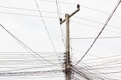 picture of messy  - electric post with messy wires on white sky - JPG