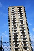 foto of public housing  - Public council housing apartments in a run down skyscraper tower block with a wire mesh fence in the foreground found in London - JPG