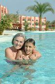 pic of grandma  - Happy smiling grandma and grandson in blue pool water - JPG