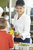 picture of school lunch  - Pupil In School Cafeteria Being Served Lunch By Dinner Lady - JPG