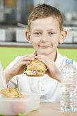 stock photo of school lunch  - Pupil Sitting In School Cafeteria Eating Healthy Packed Lunch - JPG