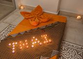 stock photo of thai massage  - Closeup detail of a Thai massage bed on the floor in luxury health spa with candles - JPG