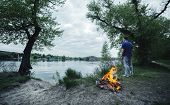 stock photo of bonfire  - Man and bonfire in the spring forest - JPG