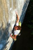 pic of climbing wall  - Young white man climbing a steep wall in mountain, rock-climbing extreme sport, summer season. ** Note: Soft Focus at 100%, best at smaller sizes - JPG