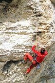 foto of climbing wall  - Young white man climbing a steep wall in mountain - JPG