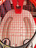stock photo of pulling  - Finished Tennis racquet freshly strung on a electronic tournament constant pull stringing machine - JPG