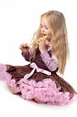 stock photo of tutu  - Little baby girl in tutu skirt playing with party blower isolated on a white background - JPG
