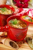 stock photo of tripe  - traditional polish tripe soup with vegetables in red ramekin - JPG