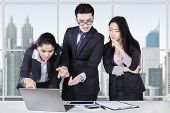 stock photo of multicultural  - Multicultural business team standing in office while discussing with laptop on desk - JPG