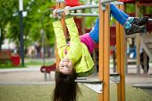 stock photo of playground  - Cute happy girl is playing on playground outdoor - JPG