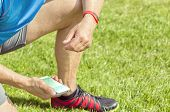 picture of kneeling  - Sportive man kneels on a lawn and checks his fitness results on a smartphone - JPG