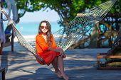 stock photo of sunbathing woman  - Woman relaxing on hammock sunbathing on vacation - JPG