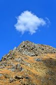 foto of cumulus-clouds  - A little white cumulus cloud seems to be in position over the rocky peak of the Kern River Canyon - JPG
