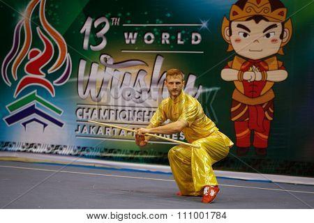 JAKARTA, INDONESIA - NOVEMBER 15, 2015: Justin Benedik of the USA performs the movements in the men's Gunshu (staff) event at the 13th World Wushu Championship 2015 held at Istora Senayan, Jakarta.