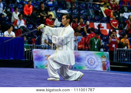 JAKARTA, INDONESIA - NOVEMBER 15, 2015: Lee Wei jen of Canada performs the movements in the women's Taijijian event at the 13th World Wushu Championship 2015 held at Istora Senayan, Jakarta.