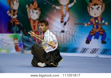 JAKARTA, INDONESIA - NOVEMBER 15, 2015: Costa Torres of Portugal performs the movements in the men's Gunshu (staff) event at the 13th World Wushu Championship 2015 held in Istora Senayan, Jakarta.