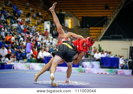 JAKARTA, INDONESIA - NOVEMBER 15, 2015: Clemente Tabugala of Philippines (red) fights Jafar Topraghlou of Iran (black) in the men's 65kg Sanda event at the 13th World Wushu Championship 2015.