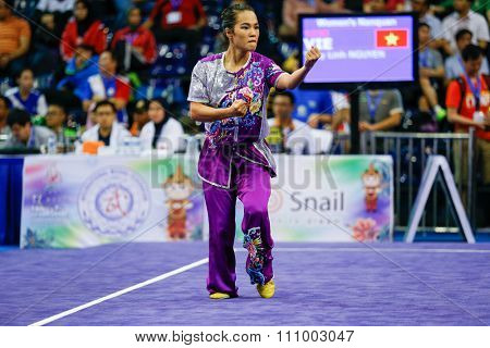 JAKARTA, INDONESIA - NOVEMBER 15, 2015: Thuy Linh Nguyen of Vietnam performs the movements in the women's Nanquan event at the 13th World Wushu Championship 2015 held in Istora Senayan, Jakarta.