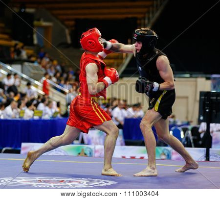 JAKARTA, INDONESIA - NOVEMBER 15, 2015: Bruce Tran of Canada (red) fights Yauhen Sliaptsou of Belarus (black) in the men's 65kg Sanda event at the 13th World Wushu Championship 2015 in Istora Senayan.
