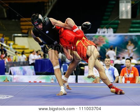 JAKARTA, INDONESIA - NOVEMBER 15, 2015: Ali Ay of Turkey (red) fights Mukesh Choudhary of India (black) in the men's 70kg Sanda event at the 13th World Wushu Championship 2015.