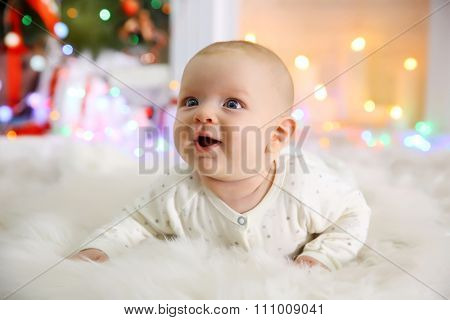 Adorable baby on the floor in the decorated Christmas room