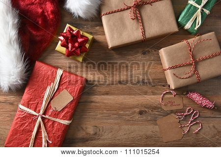 Overhead view of wrapped Christmas presents on a rustic wood table with string, gift tags, and Santa hat. Horizontal format with copy space.