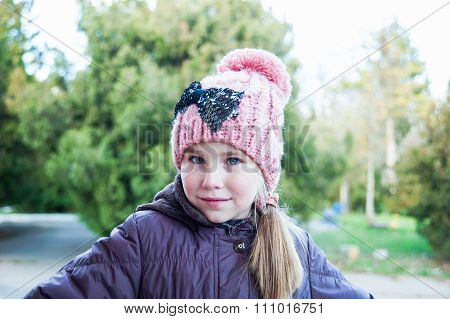 Adorable Little Girl Posing. Wearing Winter Coat And Hat.