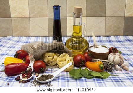 Beautiful set for the creation of the Sicilian pasta: cherry tomatoes, olive oil, balsamic sauce, garlic, spices, sea salt, salad on a rustic table.