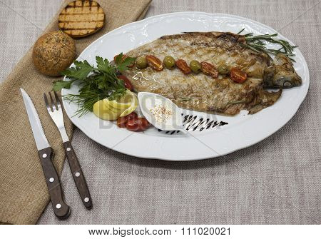 Fried fish whitefish on plate with vegetables and bread with a fork and knife