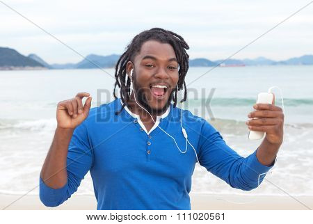 African American Guy With Dreadlocks Dancing At Beach
