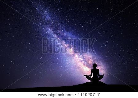Milky Way. Night sky with stars and silhouette of a woman practicing yoga.