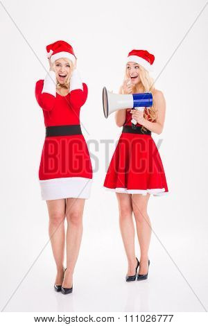Two playful blonde sisters twins in dresses of santa claus and hats joking using megaphone over white background