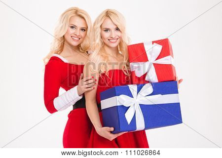 Two beautiful happy sisters twins in santa claus costumes holding gifts and looking camera over white background