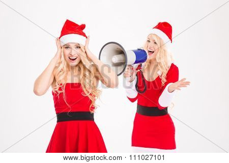 Beautiful joyful sisters twins in red santa claus costumes screaming in megaphone over white background