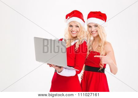 Cheerful charming sisters twins in red santa claus clothes and hats posing with laptop and pointing on it over white background
