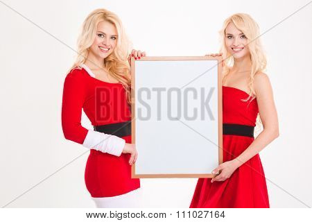 Two beautiful blonde sisters twins in santa claus clothes posing with blank board over white background