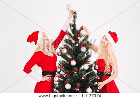 Two happy beautiful sisters twins in red santa claus costumes and hats decorating Christmas tree over white background