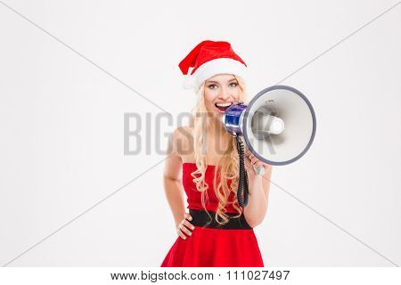 Attractive positive young blonde woman in santa claus costume talking in megaphone over white background