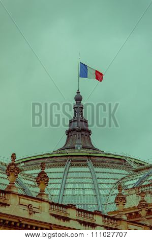 French flag swaying at the top of Grand Palais, Paris