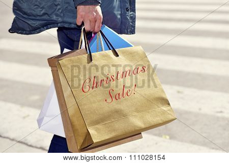 closeup of a young caucasian man with some shopping bags, one of them with the text happy christmas sale written in it, outdoors