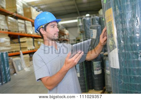 Man checking label on roll of fencing