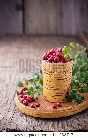 Fresh forest berries and lingonberry twigs in cup of birch bark on a wooden background.
