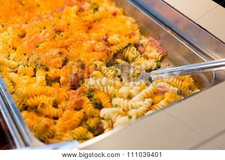 food, catering, self-service and eating concept - close up of pasta and spoon on metallic tray