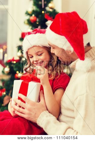 family, christmas, x-mas, happiness and people concept - smiling father and daughter in santa helper hats opening gift box