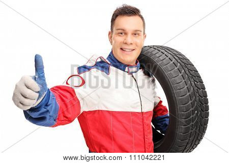 Young male car racer holding a tire and giving a thumb up isolated on white background