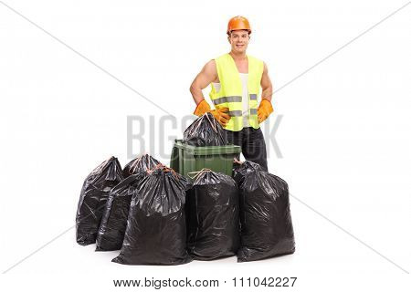 Young waste collector in green reflective vest posing behind a few trash bags isolated on white background