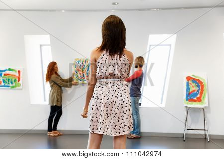Young artists in gallery hanging together painting on walls