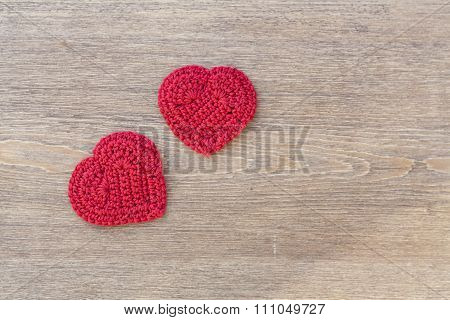 Two red crochet hearts on wooden background for Valentines day