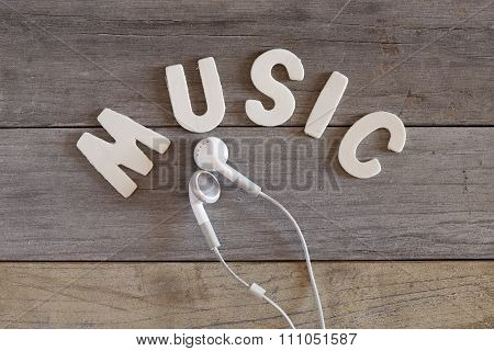 White Earbuds And Word 'music' On Wooden Table